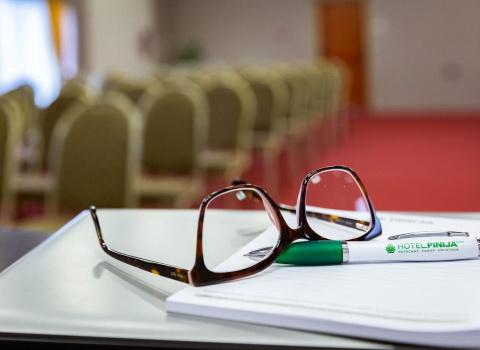 Konferencijska dvorana u hotelu, naočale i kemijska olovka