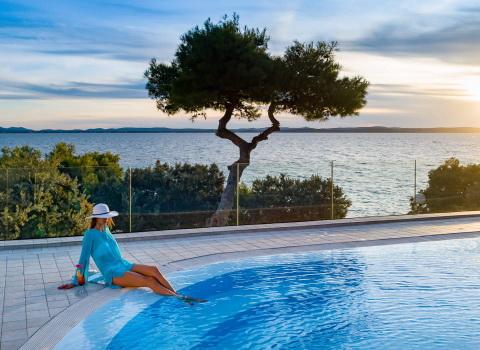Fotografija Lifestyle hotela, djevojka sjedi uz rub bazena
